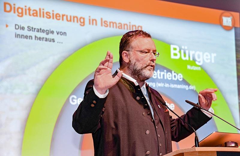 """Dr. Alexander Greulich, Erster Bürgermeister der Gemeinde Ismaning, stimmt die Teilnehmer der Vortragsveranstaltung """"Digitalisierung. Heute. In Zukunft."""" auf das Thema ein und erläutert die Digitalisierungsstrategie der Gemeinde."""